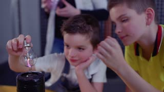 Boys watches for lightning inside electric lamp holding it over Tesla coil