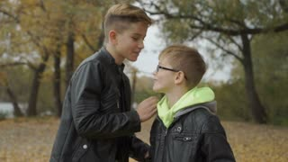 Brother whispers a secret in the ear of younger brother