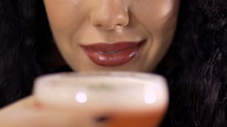Brunette drinks cocktail and smiles to camera