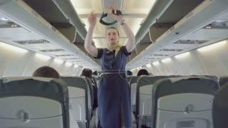Brunette stewardess explains rules of safety