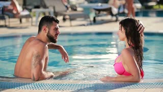 Brutal man with beard talking with beautiful brunette in the pool