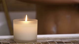 Burning candle in bathroom, woman washes her body at background