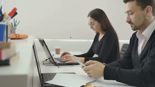 Business people works in the office, man uses tablet, woman works on laptop