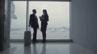 Businessman and airport worker talk near the window