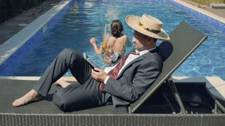 Businessman in suit and in straw hat works with tablet near swimming pool