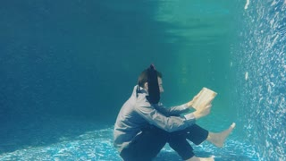 Businessman in suit read book under water