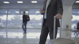 Businessman in the airport with his phone and suitcase