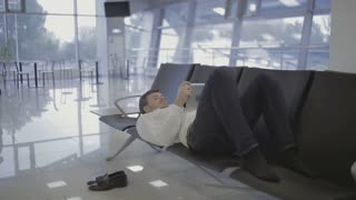 Businessman lies on the seats at the airport waiting hall and using tablet