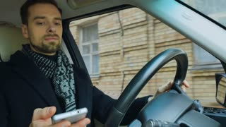 Businessman read message on phone while drives car