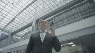 Businessman talks on phone in the airport hall