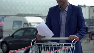 Businessman with business papers stands near a trolley