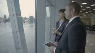 Businessman with tablet talks with airport employee near the window in airport