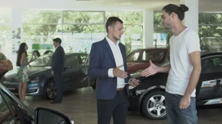 Businesspeople shakes hands after making a deal of buying car in auto showroom