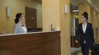 Businesswoman just arrived in a hotel and gets a room key at reception desk