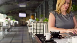 Businesswoman works in cafe on laptop