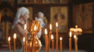 Candles is on the foreground, mother with baby on blurred background in church