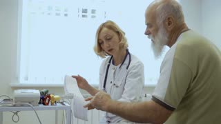 Cardiologist show results of electrocardiography to old patient