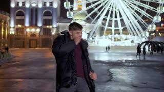 Caucasian funny guy crazy dances at ferris wheel background