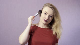Charming blonde with makeup brush