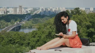 Charming brunette relax with tablet on city background