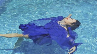 Charming brunette with red lips in blue dress swims in the pool in slowmotion