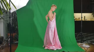 Charming girl in pink satin bedsheet poses for camera at green background