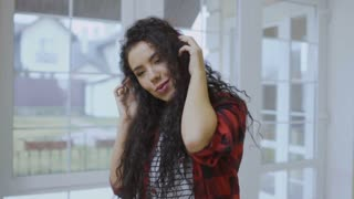 Cheerful curly brunette listens music in headphones in slowmotion