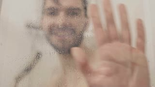 Cheerful man has fun with shower inside the shower cabin