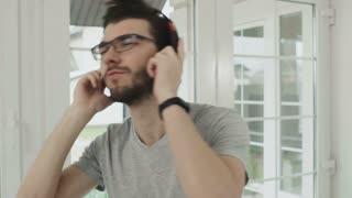 Cheerful man in eyeglasses listen music in headphones
