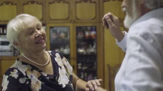 Cheerful senior woman dancing with her husband at home in slow motion