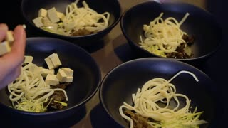 Chef add tofu to ingredients into a bowls