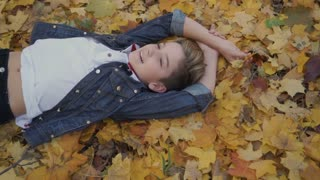 Child lying on the ground show thumb up