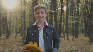 Child with the boquet of autumn leaves