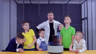 Children and laboratory assistant makes physics experiment in science museum