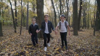 Children friends run in the forest on camera
