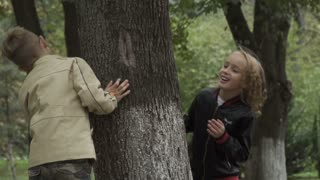 Children peer out of the big tree
