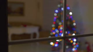 Christmas tree is lighting in the room through the window in the dark room