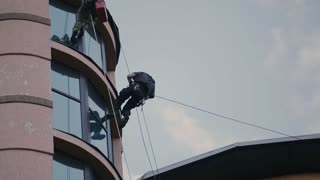 Climber jumps between the sides of the building