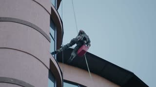 Climber with cleaning equipment outside the building
