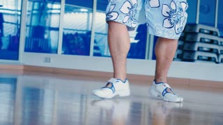 Close-up of man's legs dancing in gym