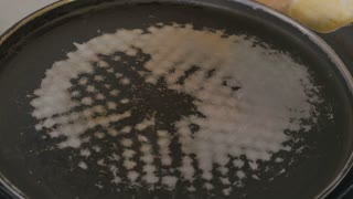 Close-up - the cook pours the oil on a hot pan