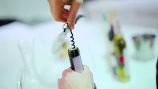 Close-up - woman open the wine bottle with corkscrew