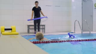 Coach show swimming exercise with noodle to elderly woman