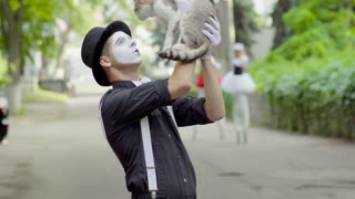 Comic mime joking with cat on the street