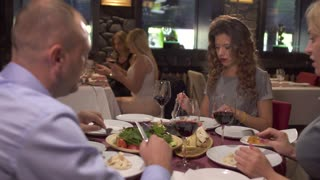 Company of adult people have a dinner at restaurant