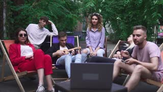 Company of young people have a rest in a summer cafe