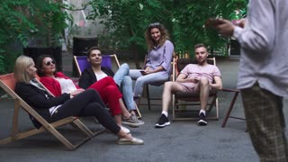 Company of young people is resting on a summer area in a cafe