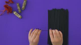 Conceptual video - woman break sticks of black spaghetti