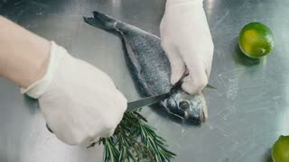 Cook cuts the fish on table