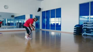 Cool man in cap and sunglasses dancing the hip-hop in the gym